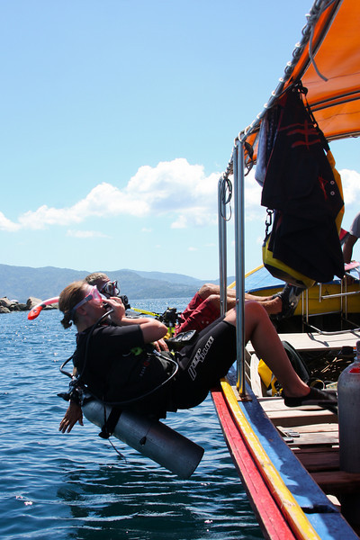 Two students perform a back roll entry out of our longtail to start a dive at Koh Weo.