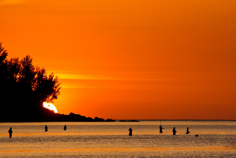 The sun goes down over Kamala Beach as a handful of local Thai Fishermen work at making a catch for dinner.