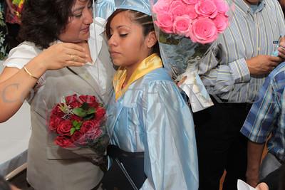 Graduate Yoselyne Nava receives flowers and a hug following Nora Cronin Presentation Academy's first graduation at Calvary Presbyterian Church on Saturday, June 12, 2010 in Newburgh, NY. Hudson Valley Press/CHUCK STEWART, JR.