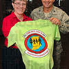 """Tribune-Star/Joseph C. Garza<br /> Deployment T: Dodie Halter, president of the 181st Intelligence Wing Family Readiness Group, and Col. Don Bonte, display the T-shirt Thursday that youngsters will wear during their """"deployment"""" Saturday."""