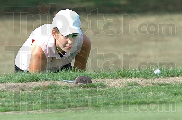 Eye, ball: North Central's Anna McClain eyes the ball on the edge of the green during match action against Terre Haute North and West Vigo Thursday afternoon at The Landing golf course.