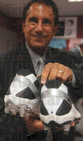 Tribune-Star/Joseph C. Garza<br /> Worn by the QB: Vigo County School Corporation Superintendent Dan Tanoos displays a pair of cleats that were once worn by New York Jets quarterback Mark Sanchez Thursday during a press conference at the school corporation's office.