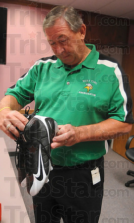 Tribune-Star/Joseph C. Garza<br /> From the Jets to the Vikings: West Vigo Athletic Director Mike Miller checks the size on a donated pair of football cleats that were worn by a New York Jets player after a press conference Thursday at the Vigo County School Corporation office.