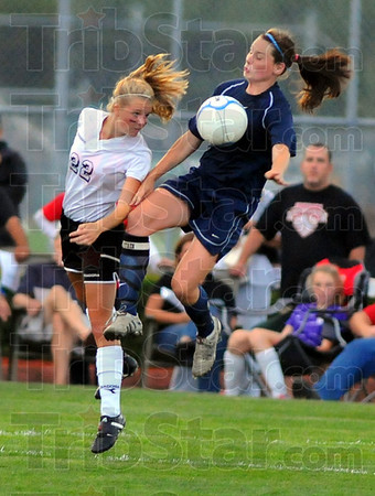 Tough as always: Brave Courtney Hubbard(22) heads the ball past the defense of Terre Haute North's Molly McKee in first half action on the Braves' pitch Thursday night.
