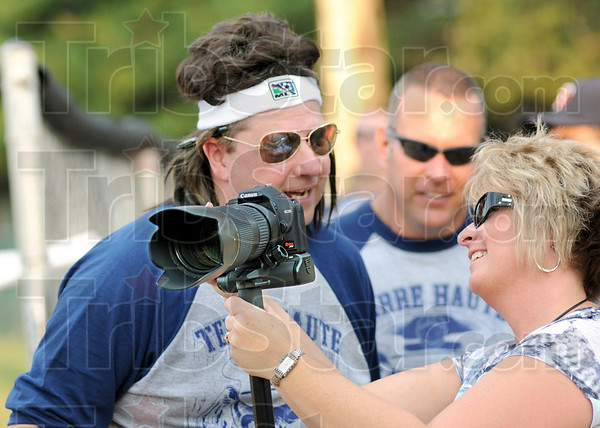 """Picture this: Natalie Trotter shows a photograph to Terre Haute police detective Troy Davis during Thursday's fundraiser for the Widows and Orphans fund. Davis is wearing a """"Joe Dirt"""" wig during the event. Chief John Plasse watches from a distance (center)."""