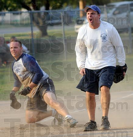 "Pumped: Terre Haute police officer Justin Sears (L) looks to the umpire (Mayor Duke Bennett) for a call during Thursday's Widows and Orphans fundraiser. Third baseman Brett Doan reacts to the ""out"" call."