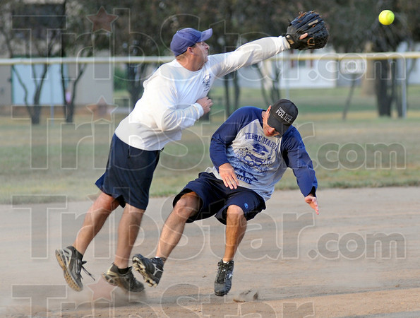 Safe: Terre Haute firefighter Brett Doan reaches for an incoming throw to third base as officer Rob Pitts makes it safely to the bag during Thursday's Widows and Orphans fundraiser.