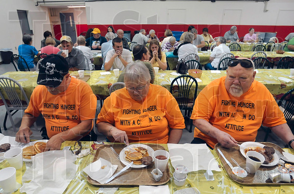"""Tribune-Star/Joseph C. Garza<br /> """"Can"""" do attitude: Jim Flanders, Marilyn Flanders and Pastor Carl Leth of the Jasonville United Methodist Backdoor Food Pantry dig into their stacks of hot pancakes as they attend the hunger awareness breakfast Thursday at Ryves Youth Center at Etling Hall."""