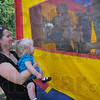 Not yet: Dixie Russell holds her daughter Sophia outside the bounce house at the get together Sunday afternoon. Several families with a Down Syndrome child have formed the STAR playgroup.