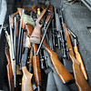Guns & Ammo: The trunk of a Terre Haute police cruiser is loaded with dozens of guns confiscated from Brian Acklin's 1936 Plum Street residence Sunday afternoon.