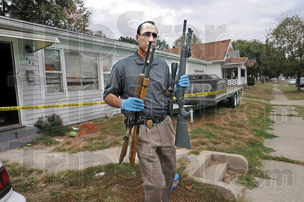 Weapons: Terre Haute police detective Brad Rumsey carries weapons from the  home at 1936 Plum Street Sunday afternoon. Police recovered dozens of rifles, shotguns and handguns from the scene of a shooting.