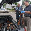 Confiscated: Terre Haute police officer Mike McGuire and Detective Brad Rumsey unload weapons before putting them into the trunk of a police car Sunday afternoon at 1936 Plum Street.