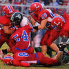 Seeing red: West Vigo Runningback Cole Lydick is brought down by a sea of red. Linton defenders include Ethan Lannan(54), Brock Moore(56), Kent Helton(8), and Anthony Morin(65).