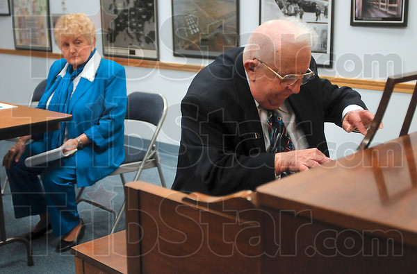 Tribune-Star/Joseph C. Garza<br /> From the heart: Michael Kor plays a musical number on the piano as his wife, Eva Kor, looks on after Michael signed a letter of forgiveness to the Nazis Friday at the CANDLES Holocaust Museum.