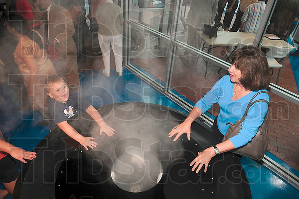 Tribune-Star/Joseph C. Garza<br /> Their heads in the clouds of science: Four-year-old Rylee Williams operates the cloud machine with some help from Karen Propst Friday at the museum.