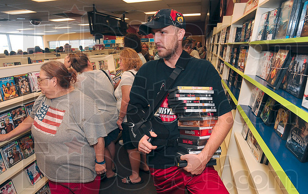 Tribune-Star/Joseph C. Garza<br /> One arm? No problem: Blockbuster Video customer John McCalister holds onto his videos with one arm as he waits in line at the video store Friday.