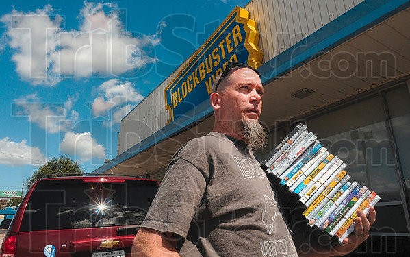 Tribune-Star/Joseph C. Garza<br /> Expanding the family library: Andre Bonter carries a stack of DVDs from the Blockbuster Video store on Third Street during the store's liquidation sale Friday.