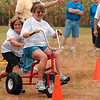 Tribune-Star/Joseph C. Garza<br /> Hoosier Heating & Cooling employee Ronda Hennis gets some help from co-worker Maureen Coughlin as Hennis tackles the tricycle competition of Corporate Olympics Saturday at Forest Park.