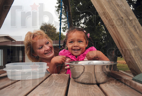 Tribune-Star/Joseph C. Garza<br /> We help Grandma with chores: Amia Dyer, 3, can't help but laugh as her grandmother, Ruthie LaTelle, holds her up to place a fresh bowl of water out for the family cat Friday at LaTelle's home near Prairieton.