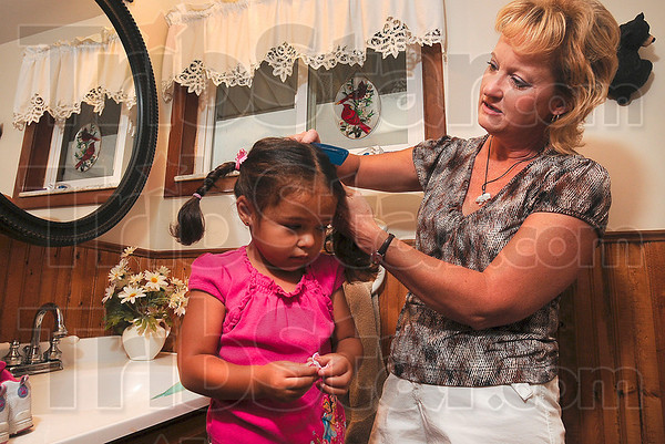 Tribune-Star/Joseph C. Garza<br /> Sleepyhead: Ruthie LaTelle works with her granddaughter, Amia Dyer, 3, to comb her hair even though the combing is the least favorite part of Amia's morning Friday at LaTelle's home near Prairieton.