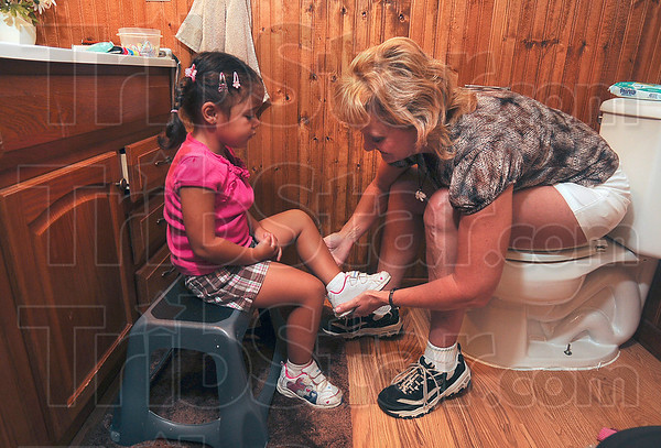 Tribune-Star/Joseph C. Garza<br /> Rising little ones...again: Ruthie LaTelle puts shoes on her granddaughter Amia's feet after she dressed her and combed her hair Friday morning before school at LaTelle's home near Prairieton.