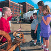 The old way: David Hemrich demonstrates the ancient way of spinning wool into yarn to Paul David Alger IV, his sister Isabel Alger and their aunt Holly Tipton. They were visiting the Street Fair Friday evening.