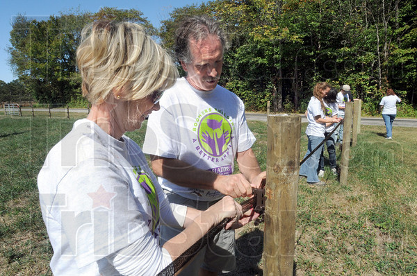 Mending fences: Denise Hoke and Don Lorenzen install electric fencing along the perimeter of the Peacefield Equine Sanctuary Saturday afternoon.