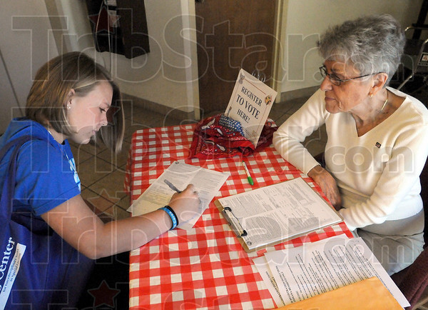 Registration: Indiana State University student Brooke Wininger registers to vote at the Vigo County Public Library Saturday mornng. League of Women Voters volunteer Barbara Mullen assists.