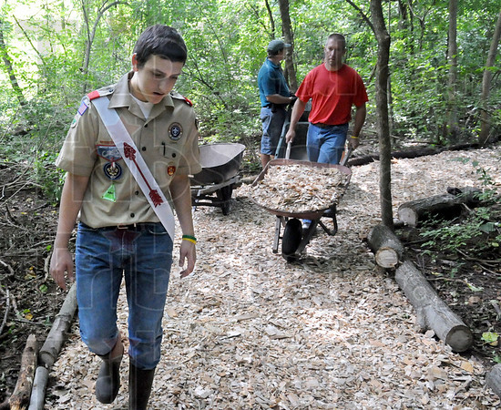 This way: Eagle Scout candidate Saxon Porter (L) supervises the spreading of wood chips onto the newly constructed walking trail through Dobbs Park Satuday morning. Pushing the wheel burro is Dave Ankerman.