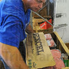 Lots to manage: Bill Haley, warehouse manager for the Catholic Charities Food Bank, carries a box of meats to a freezer.