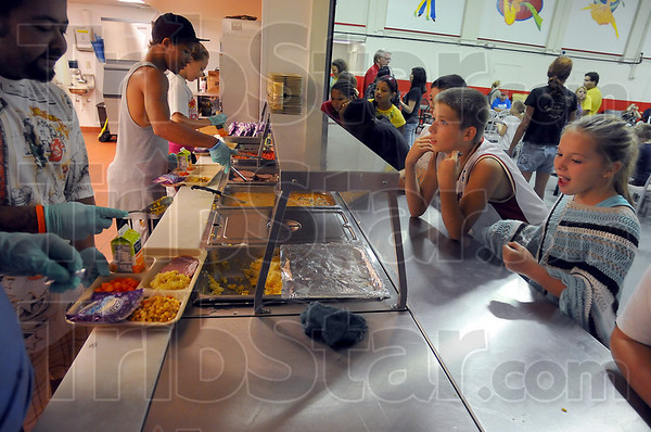 Needed service: Servers fill trays for the older children at the 5:00p.m. mealtime at Ryves Hall Friday evening. Younger children get their food about an hour earlier.