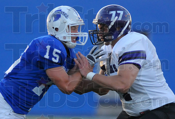 New role: Sycamore Ryan Roberts, now a defensive back, tries to get past the defense of Puma Wes Schroeder.
