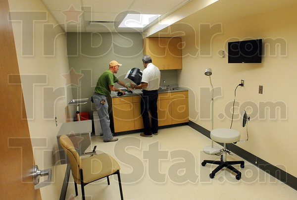 Getting ready: Hannig Construction employees Wayne Rowley and John Kastigar install a paper towel dispenser in one of the examination rooms at the Employees Health and Wellness clinic at the VCSC general services facility Wednesday afternoon.