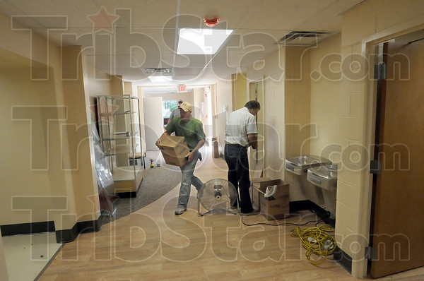 Preparations: Workers carry items to be installed in the examination rooms of the new VCSC Employees Health and Wellness Clinic Wednesday afternoon.