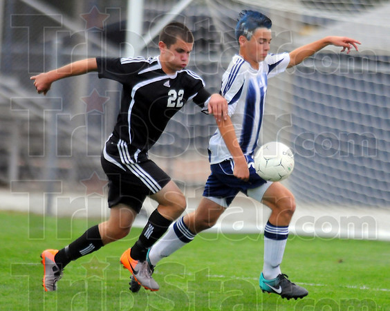 On his way: Terre Haute South team captain Nic Henderson(22) competes with Patriot Ricky Pemberton for control of the ball. Henderson had a hat trick against the Braves' cross-town rivals.