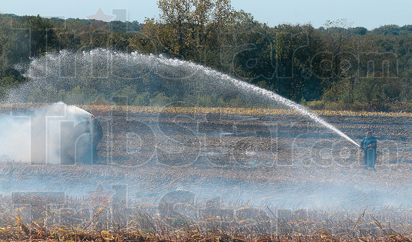 Tribune-Star/Joseph C. Garza<br /> Field aflame: A Terre Haute Fire Department firefighter sprays water on a smoldering milo bail in a field off of north 13th Street Wednesday.