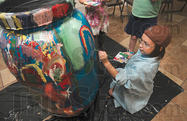 Tribune-Star/Joseph C. Garza<br /> Troop 2995 Brownie Seaaira Bendzsa adds her own creation in paint to a rain barrel as she and other brownies and daisies paint the barrel in the Seelyville Town Hall Wednesday.