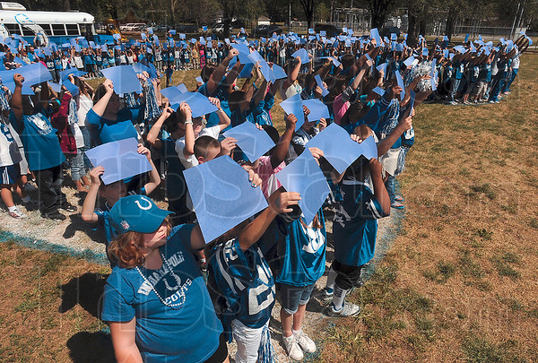 Tribune-Star/Joseph C. Garza<br /> Go Horse!: Ouabache Elementary fifth-grader Brittani Leclerck, lower left, holds up a blue sheet of construction paper along with the rest of the school's students as they form a giant horseshoe for a photo Monday at the school.