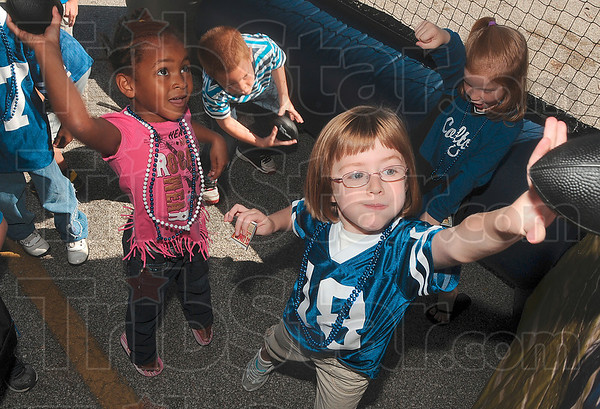 Tribune-Star/Joseph C. Garza<br /> Watch out, Peyton: Ouabache Elementary kindergartners Lela Oliver and Abbie Staggs try to throw miniature footballs through targets in the Peyton Manning football toss during the school's festivities Monday at the school.