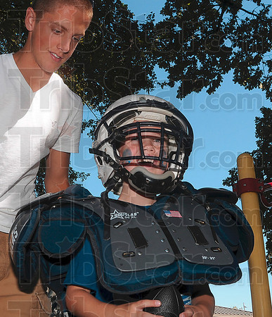 Tribune-Star/Joseph C. Garza<br /> Like the big kids: Ouabache Elementary first-grader Dalton Brown, 6, is all smiles as he wears a Terre Haute North football helmet and shoulder pads while North's Chad Holler looks on Monday at the school.