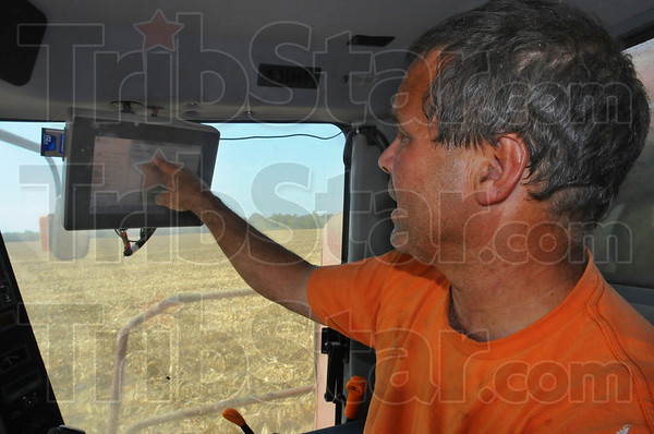 Good yield: Denny Bell looks over teh computer readout in the cab of his combine. The screen was showing an average of 222 bushels per acre in this field.
