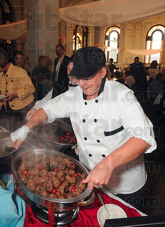 Tribune-Star/Joseph C. Garza<br /> Fresh from the kitchen: Chef Debbie Eckhart of Sodexo replaces an empty container of lamb meatballs with a full one during the March of Dimes' Culinary Stars fundraiser Monday at St. Mary-of-the-Woods.