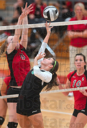 Tribune-Star/Joseph C. Garza<br /> A soft touch: West Vigo's Caitlyn Tilford finesses the ball over the net as Terre Haute South's Morgan Taylor attempts to block while Taylor's teammate Madison Steward looks on during the Vikings' match against the Braves at South Monday.