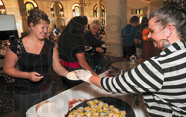 Tribune-Star/Joseph C. Garza<br /> Try this: Amy Lindsey of Brazil accepts a portion of Italian beef from Mogger's Lisa Rogers during the March of Dimes' Culinary Stars event Monday at St. Mary-of-the-Woods.
