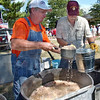 Plenty enough: Carl Gregory dishes a scoop of bean soup to Paul Bridgewater to carry to the servers at the traditional bean dinner at Fairbanks Park Monday afternoon.