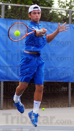 #2: Chris Holcomb goes airborne to return a shot from Austin Foster in their part of the crosstown tennis match Tuesday evening  on the Patriots' courts.