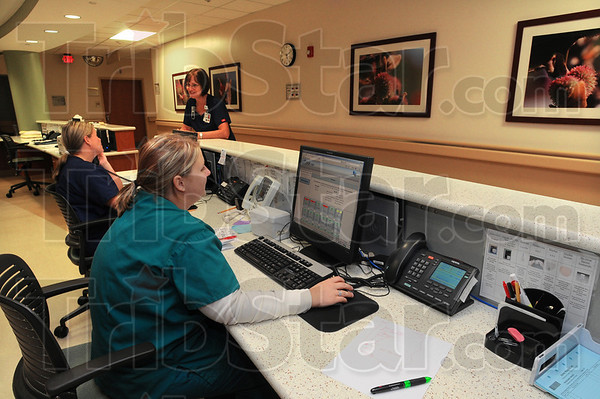 Good environment: Nurses Kristin Phillips and Elaine Shoemaker confer in the background while Patient Care Assistant Melissa Wyatt works at a computer terminal on Union Hospitals' third floor Tuesday afternoon.