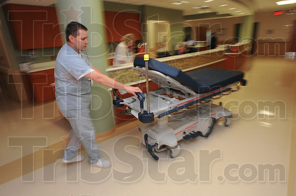 On the move: Union Hospital transporter Kevin Hoggatt wheels a bed through a nurses station Tuesday.