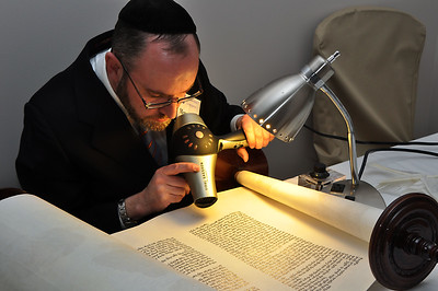 Behind the ark, Rabbi Youlus helps the ink of the final five letters dry (photo by Sam Backman)
