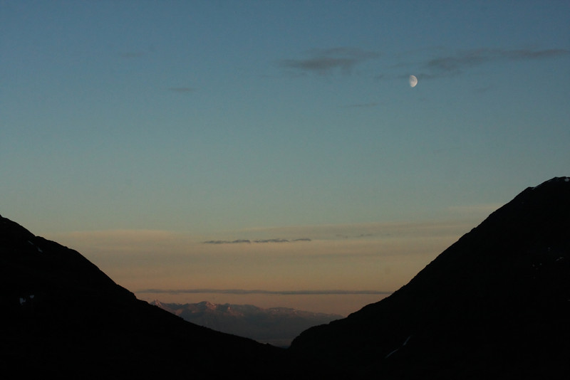 A setting moon sinks over the Matanuska-Susitna Valley at almost midnight the day before summer solstice.